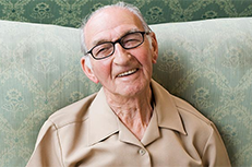 senior man smiling on green couch
