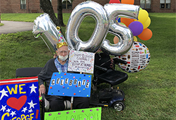 George with his birthday balloons and signs