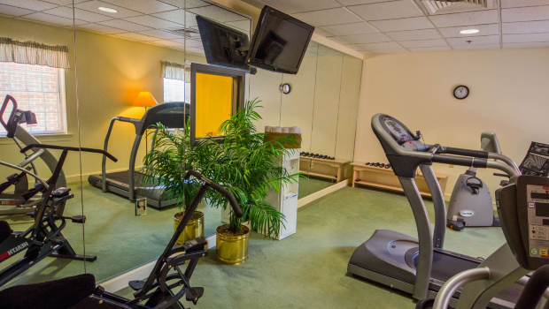 exercise room with elliptical machines and a TV