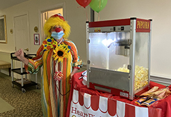 team member in clown costume with popcorn cart