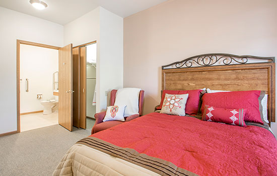 a bedroom with a large red bed and an easily accessible bathroom