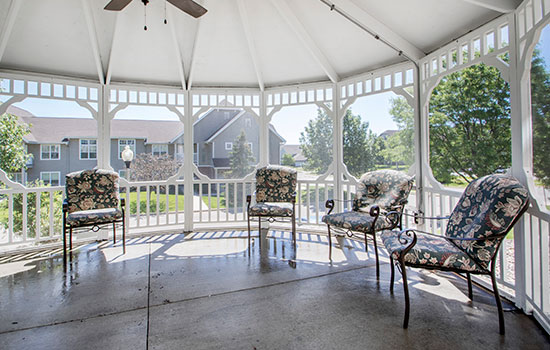 large gazebo with a ceiling fan and chairs in the backyard