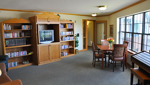 lounge area with book shelves and a television