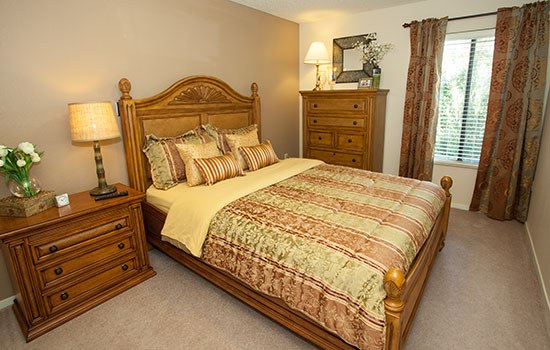 bedroom with a nicely made bed and wooden drawers