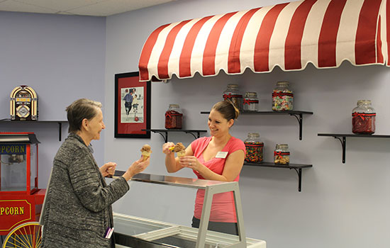 an employee serving a resident at the ice cream bar