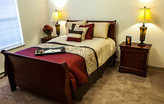 bedroom with a nicely made maroon bed and two reading lamps