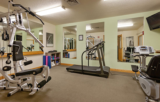 exercise room with elliptical and weight machines