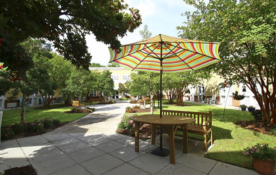 patio with a paved walkway and a table with an umbrella