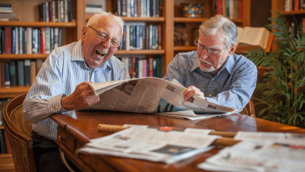 two men reading the newspaper together in the library