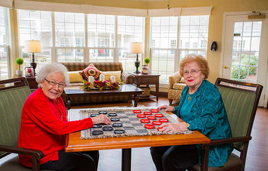 two residents playing a board game in the game room