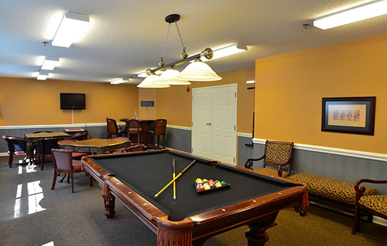 billiards room with a black pool table and chairs for seating
