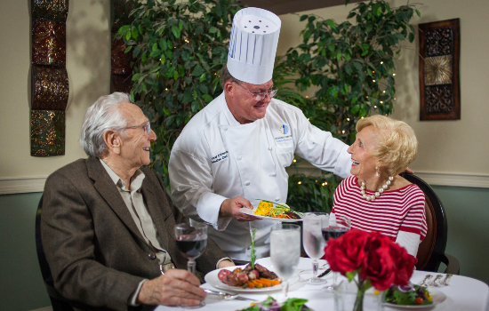 chef serving a delicious meal to two residents