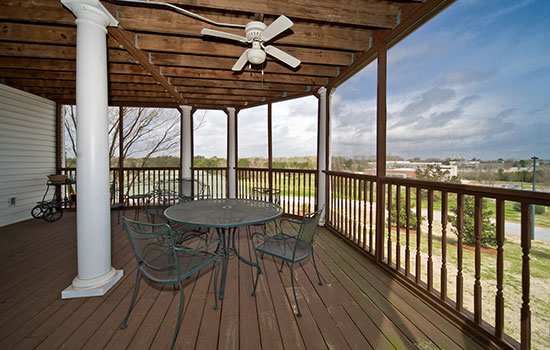 spacious balcony with a table and a ceiling fan