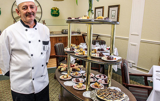 chef with a cart of delicious desserts