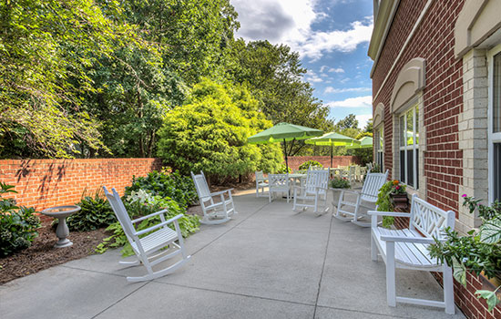 outdoor patio with rocking chairs and umbrellas for shade
