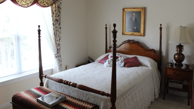 a bedroom with a large white bed and nice drawers