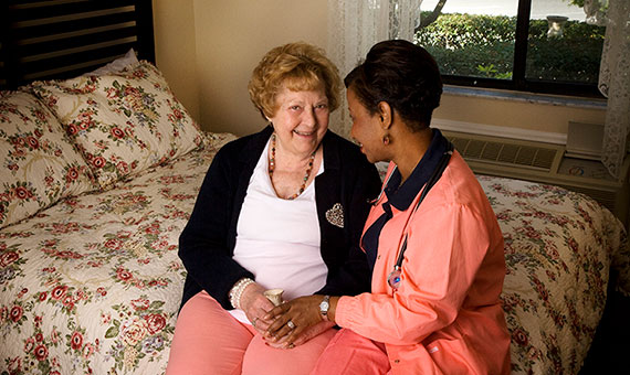 resident and caregiver sitting on bed
