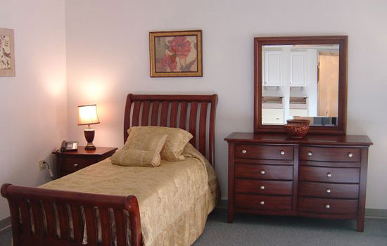 a bedroom with a nicely made bed and a wooden bureau