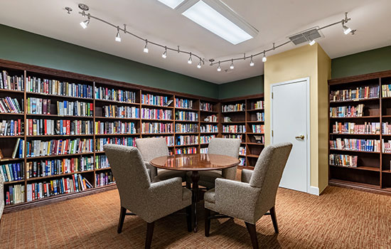 library with many books and a round table