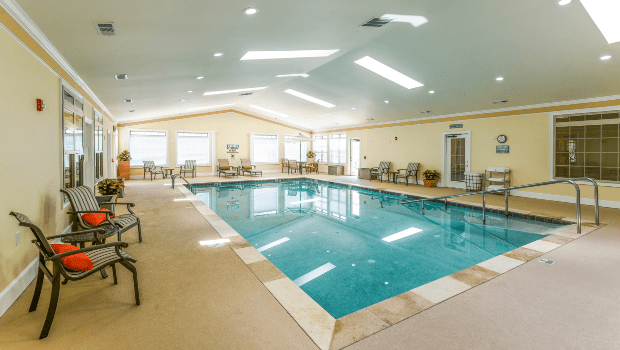 large indoor pool surrounded by chairs