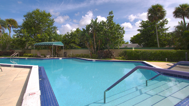 large outdoor swimming pool with a shaded place to sit