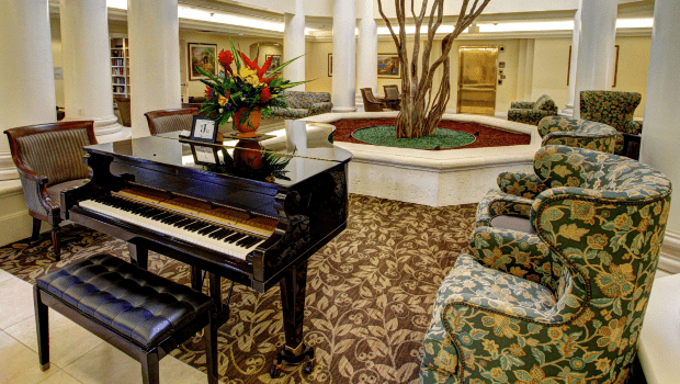 spacious lounge with a piano and nice chairs