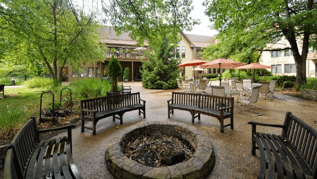 outdoor patio with benches for relaxing under trees