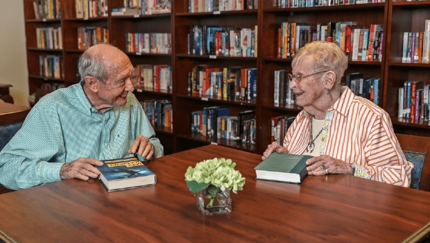 two men conversing at a table in the library