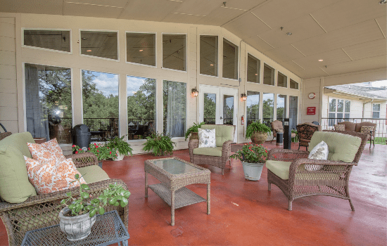 large outdoor patio with lounge chairs, tables, and a high overhang