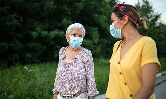 mother and adult daughter walking with face masks