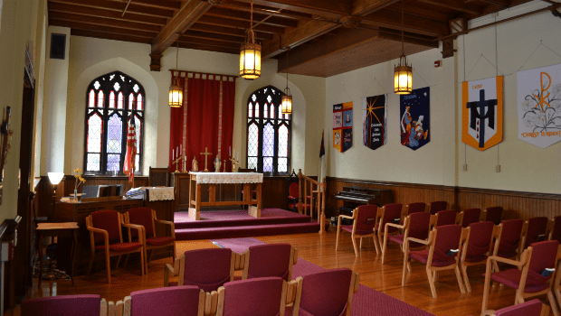 large cathedral room with rows of benches and a stage