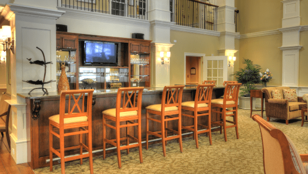a bar in the lounge with bar chairs and a TV