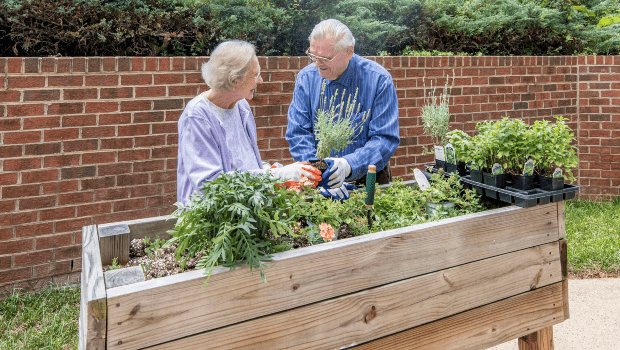 two residents tending to a flower box outside