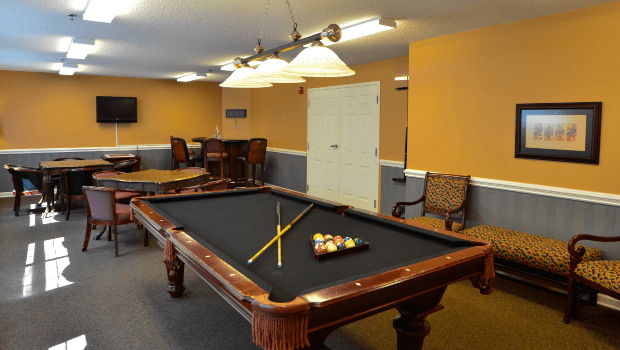 billiards room with a nice black pool table and chairs for seating