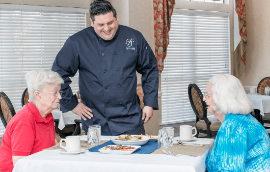 chef serving two women a meal in the dining room