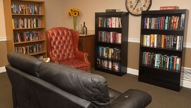 library with multiple book shelves and a sofa