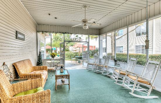 indoor porch with many windows and lounge chairs