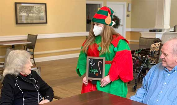team member in elf costume wearing face mask and two residents