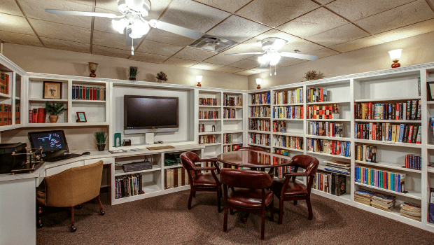 cozy library with many books, a TV, and a place for your laptop