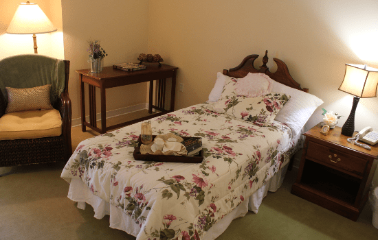 bed with white floral comforters and a personal lounge chair