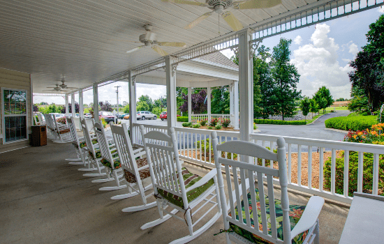spacious porch with rocking chairs and an overhang