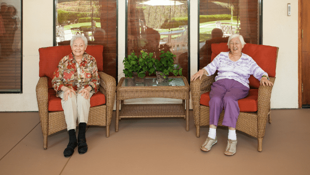 two residents in lounge chairs on the porch