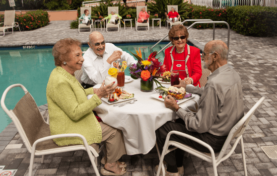 a group of friends enjoying lunch outside by the pool