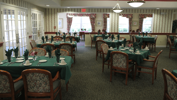 restaurant style dining room with many green tables