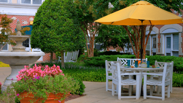 very nice outdoor patio with gardens and a table with a large umbrella