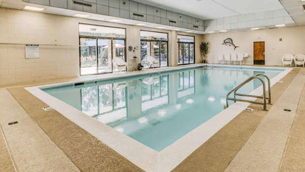 indoor swimming pool with chairs on the side