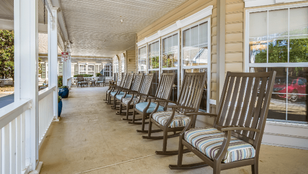 long outdoor porch with many rocking chairs