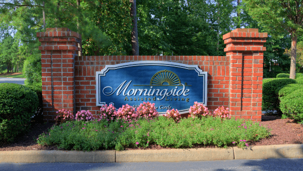large brick welcome sign in front of the residency