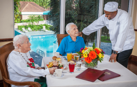 chef serving two residents a delicious meal