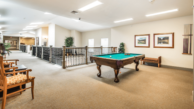 spacious lounge area upstairs with a billiards table